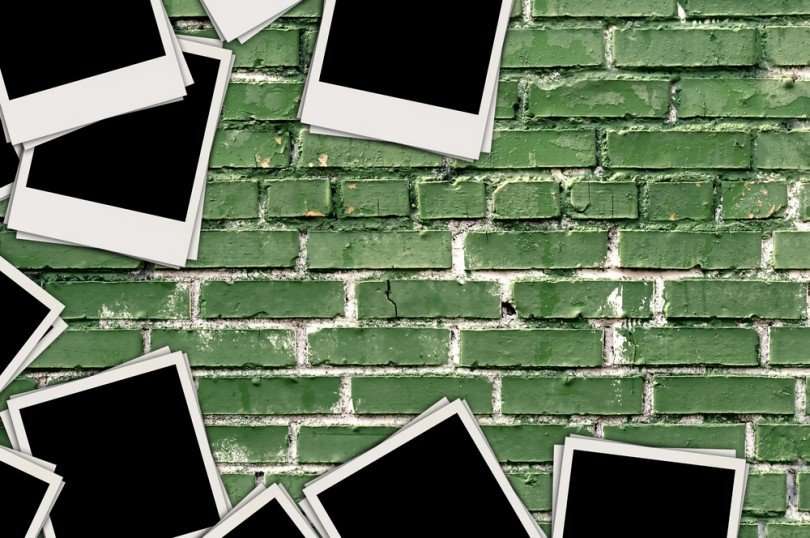 Blank photos on scattered on a green brick background